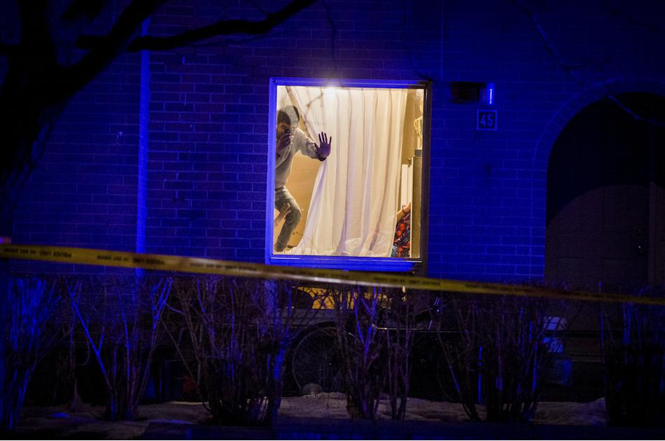 A man takes a picture with his cell phone out of his window at a crime scene that police have closed off at Queen Frederica Drive in Mississauga, Ontario