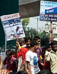 Indian vendors hold placards denouncing Walmart during a strike at the Azadpur wholesale vegetable and fruit market in New Delhi on September 20. Up until now foreign groups such as Walmart could only operate as wholesalers amid fears that big Western retail chains would swamp India's tens of millions of small family-run stores which dominate the sector