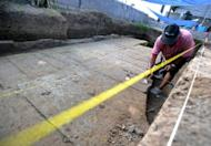 An archeologist excavates the remains of an ancient Hindu temple in Denspasar on Indonesia's Bali island on October 25, 2012. Construction workers have discovered what is thought to be the biggest ancient Hindu temple ever found on the Indonesian island