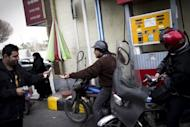 Iranians line up at a petrol station to fuel their motorcycles in central Tehran on February 19, 2012. The United States says it will exempt seven emerging economies including India from tough new sanctions after they cut back on oil from Iran, but the punishment still loomed for China