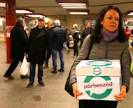 Timea Szabo, co-chair of opposition party Parbeszed Magyarorszagert hands over documents with signatures supporting a referendum on Budapest's 2024 Olympic bid to political movement Momentum at a stand in Budapest, Hungary, February 16, 2017. Picture taken February 16, 2017. REUTERS/Laszlo Balogh