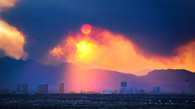The Las Vegas Strip skyline is seen as smoke continues to billow from the Carpenter 1 fire on Mount Charleston on Monday, July 8, 2013 in Las Vegas. Homes were threatened, but more than 750 firefighters, including 18 elite Hotshot crews, were battling the Carpenter 1 Fire some 25 miles northwest of Las Vegas, said Jay Nichols, a U.S. Forest Service spokesman in the Spring Mountains National Recreation Area. (AP Photo/Las Vegas Review-Journal, David Becker)