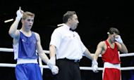 Jeremy Beccu (L) of France and Birzhan Zhakypov (R) of Kazakhstan await the verdict following their Light Flyweight (49kg) boxing match of the London 2012 Olympics at the ExCel Arena in London. Zhakypov was awarded a close 18-17 points decision