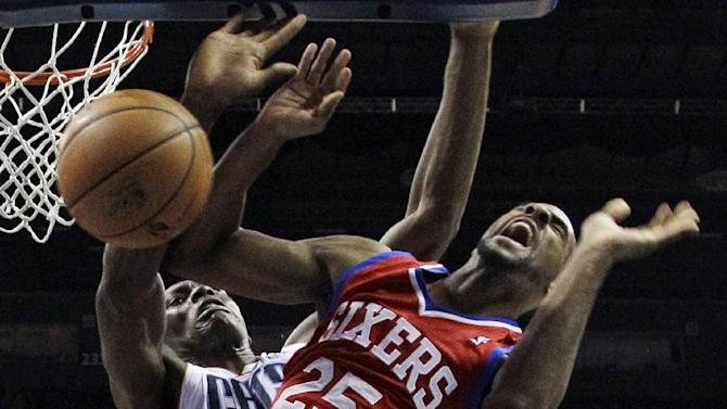 Philadelphia 76ers' Elliot Williams, front, is fouled by Charlotte Bobcats' Bismack Biyombo, back, during the first half of an NBA basketball game in Charlotte, N.C., Friday, Dec. 6, 2013