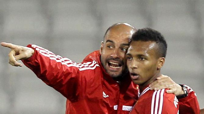 Bayern Munich's coach Pep Guardiola, left, and player Dante talk on the sidelines during his team's friendly football match against Al-Merreikh at Al-Saad stadium in Doha on Thursday, Jan. 9, 2014