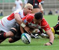 Tonga's scrum-half Taniela Moa (L) tackles Japan's centre Ryan Nicholas during their match at the Pacific Nations Cup rugby union tournament in Tokyo. Tonga defeated Japan 24-20