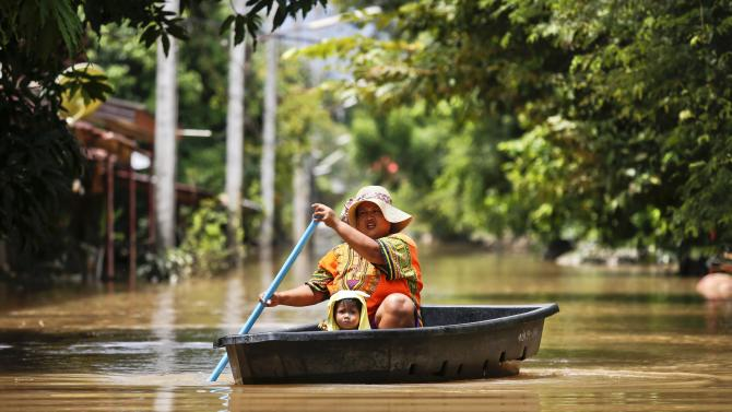 A woman and her child travel along a flooded street by boat at Kabin Buri district in Prachin Buri