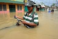 A resident pushes his bicycle through murky floodwaters in the aftermath of Typhoon Nalgae in Calumpit. The Philippines deployed helicopters, inflatable boats and amphibious vehicles Sunday in a desperate bid to evacuate tens of thousands in the aftermath of successive monster storms
