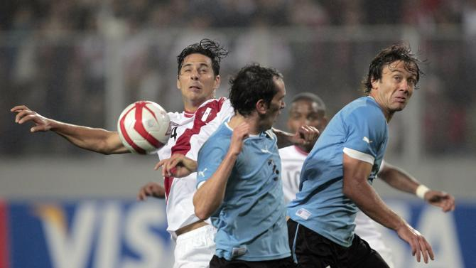 Peru's Pizarro battles for the ball with Uruguay's Lugano and Godin during their 2014 World Cup qualifying soccer match in Lima