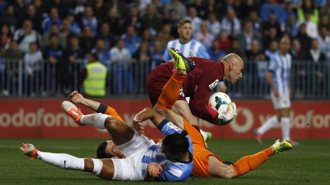 Malaga's goalkeeper Willy Caballero catches the ball as his team mate Angeleri and Real Madrid's Bale fall on the pitch during Spanish First Division soccer match in Malaga