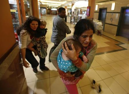 Women carrying children run for safety as armed police hunt gunmen who went on a shooting spree in Westgate shopping centre in Nairobi September 21, 2013. The gunmen stormed the shopping mall in Nairobi on Saturday killing at least 15 people in what Kenya's government said might be a terrorist attack, and sending scores fleeing into shops, a cinema and onto the streets in search of safety. Sporadic gun shots could be heard hours after the assault started as soldiers surrounded the mall and police combed the building, hunting down the attackers shop by shop. Some local television stations reported hostages had been taken, but there was no official confirmation. REUTERS/Goran Tomasevic