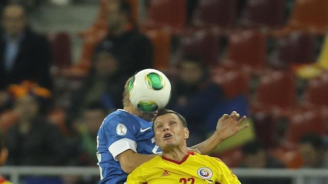 Taijo Teniste, top left, of Estonia and Gheorghe Bucur of Romania, front right, jump for a header during the World Cup Group D qualifying soccer match at the National Arena stadium in Bucharest, Romania, Tuesday, Oct. 15, 2013