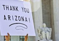 A supporter of Arizona's tough immigration law holds a sign in front of the Supreme Court