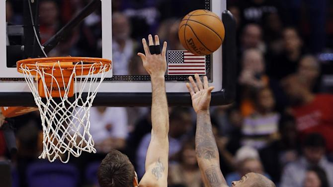 Portland Trail Blazers' Joel Freeland (19) tries to block the shot of Phoenix Suns' P.J. Tucker during the first half of an NBA basketball game, Wednesday, Nov. 27, 2013, in Phoenix