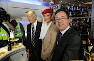 Qantas Chief Executive Alan Joyce (R) and Emirates President Tim Clark (3rd R) pose for a photo on board an Emirates aircraft, at Sydney Airport, on September 6, 2012. Australia's competition watchdog on Thursday gave its preliminary approval to a global alliance between struggling Qantas and Dubai-based Emirates, but only for five years initially