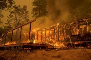 File photo of a home burning in the Butte Fire near Mountain Ranch