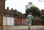 A woman walks past garages near the High Street in Stratford, east London on August 15, 2012. London may have basked in the euphoria of a successful Olympics in 2012 but now that the party is over, local people are wondering if its legacy can improve the deprived area which hosted the Games