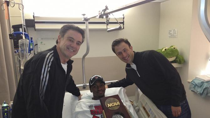 In this photo released by the University of Louisville, injured Louisville guard Kevin Ware lies in a hospital bed holding the NCAA Regional Championship trophy flanked by coach Rick Pitino, left, and former Louisville assistant coach Richard Pitino, Monday, April 1, 2013, in Louisville, Ky. Ware broke his leg in the first half of Sunday's Midwest Regional final when he landed awkwardly after trying to contest a 3-point shot, breaking his leg in two places. He was taken off the court on a stretcher as his stunned teammates openly wept. His teammates went on to defeat Duke 85-63 to reach their second straight Final Four. (AP Photo/University of Louisville, Kenny Klein)