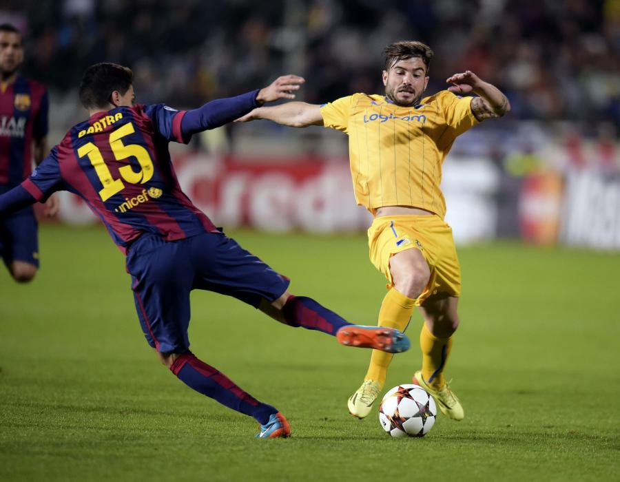 APOEL Nicosia's Gomes fights for the ball with Barcelona's Bartra during their Champions League Group F soccer match in Nicosia