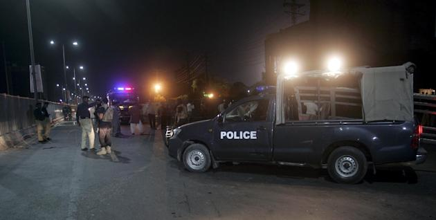 Pakistani police officers gather at the site of  suicide bombing on a road leading to Gaddafi Stadium late night on Friday, May 29, 2015 in Lahore, Pakistan. A suicide bomber blew himself up Friday ne