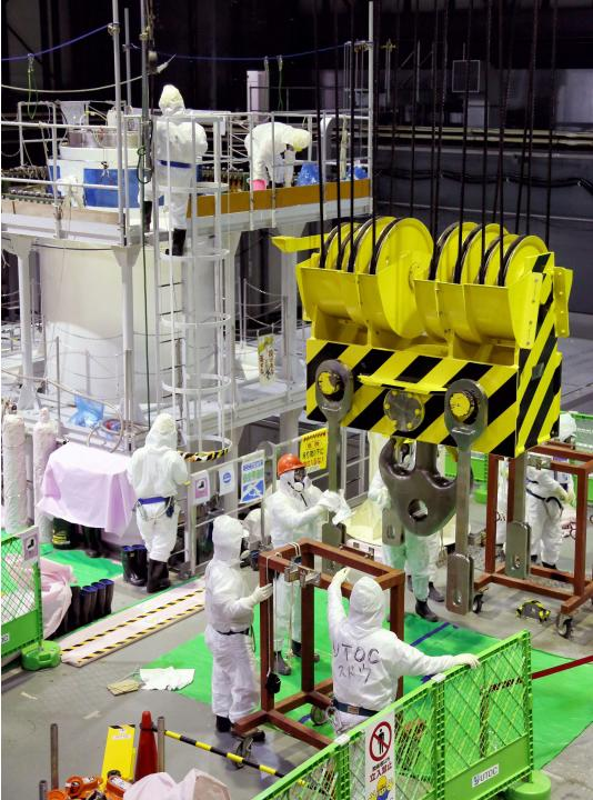 Workers in protective suits conduct decontamination operation in the No.4 reactor building at the tunami-crippled TEPCO Fukushima Daiichi nuclear power plant