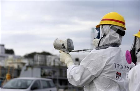 A Tokyo Electric Power Co. (TEPCO) employee wearing a protective suit and mask uses a survey meter at the tsunami-crippled TEPCO's Fukushima Daiichi nuclear power plant in Fukushima prefecture November 7, 2013.REUTERS/Tomohiro Ohsumi/Pool
