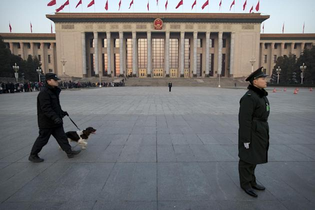 A Chinese paramilitary policeman, right, stands guard in front of the Great Hall of the People as a security officer walks past with a search dog before the opening session of the annual National Peop