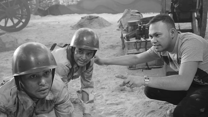 "In this undated photo released by Forward Entertainment, Filipino director Borinaga Alix Jr., right, instructs actors on the set of his film ""Death March"" inside a studio in suburban Marikina, east of Manila, Philippines. Alix chose to film ""Death March"" in black-and-white and almost entirely inside a studio using hand-painted backdrops, with close-ups of actors' painted faces portraying their struggles with nightmares and hallucinations in one of the bloodiest episodes of World War II. (AP Photo/Forward Entertainment) NO SALES"