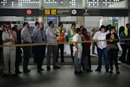 Airport employees wait near the fast-food area of Benito Juarez international airport Terminal 2, in Mexico City, after three police officers were shot dead in a shootout with alleged drug traffickers on June 25, 2012