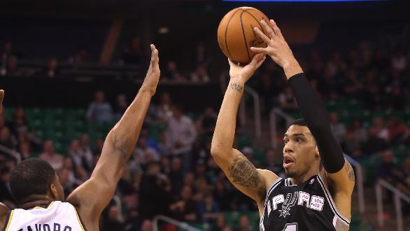 Utah Jazz's Derrick Favors (15) defends as San Antonio Spurs' Danny Green (4) shoots in the first half of an NBA basketball game on Saturday, Dec. 14, 2013, in Salt Lake City