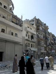 "Syrians walk past buildings damaged by bombing by the Syrian regime forces in the northern Syrian city of Aleppo. Regime aircraft hammered insurgent bastions nationwide on Sunday as rebels said they now control most of the country and have moved their command centre from Turkey to ""liberated areas"" inside Syria"