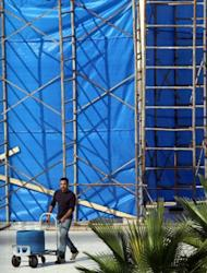 A Palestinian worker walks past a plastic tarp erected around the mausoleum of the late Palestinian leader Yasser Arafat, in the West Bank city of Ramallah, on November 24. One of the Middle East's greatest political mysteries will come a step closer to being solved on Tuesday when scientists exhume Arafat's remains to see if he was poisoned