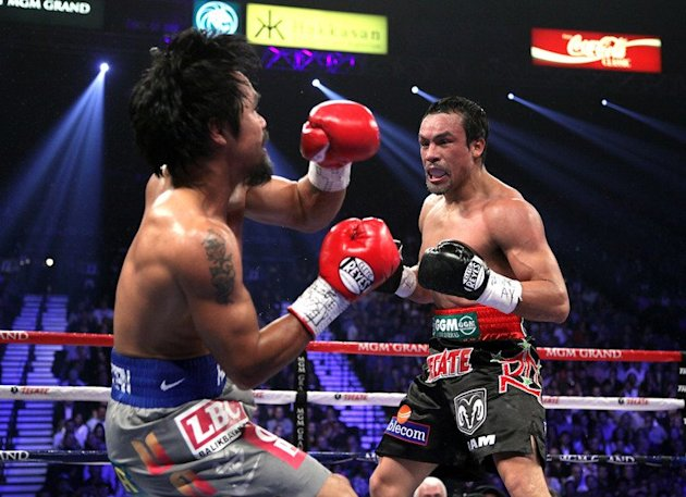 Manny Pacquiao (L) falls to to the canvas after taking a punch from Juan Manuel Marquez in the third round of their welterweight fight on December 8, 2012 in Las Vegas. Marquez knocked out Pacquiao in the 6th round