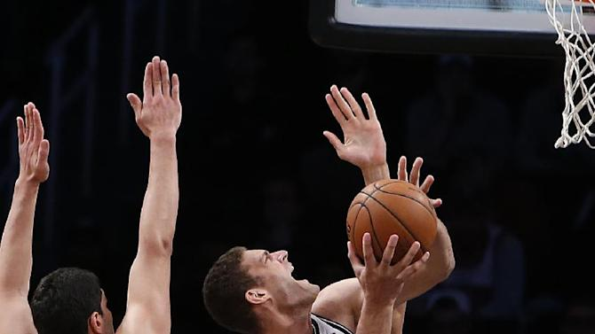 Brooklyn Nets' Brook Lopez, center, shoots against Utah Jazz's Enes Kanter (0) and Rudy Gobert, rear, during the second half of an NBA basketball game Tuesday, Nov. 5, 2013, in New York. Brooklyn won 104-88