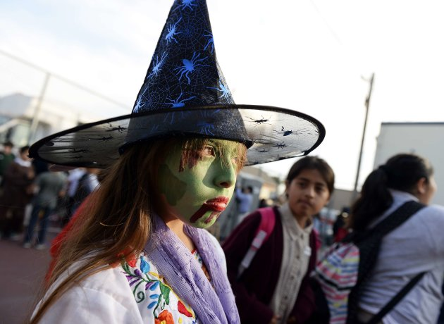 This witch may be glum, but at least she got to dress up in costume for Halloween at school. (Reuters)