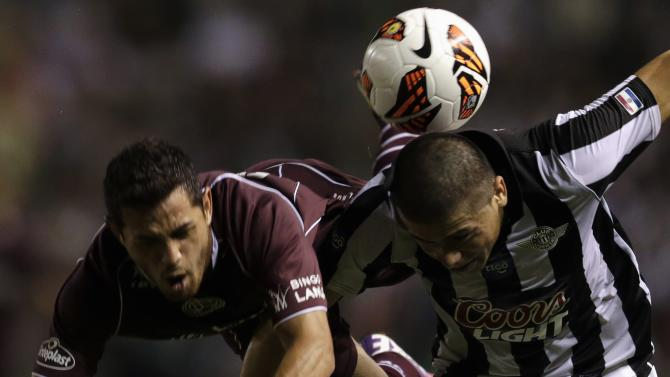 Acosta of Argentina's Lanus challenges Moreira of Paraguay's Libertad during their Copa Sudamericana semifinal soccer match in Asuncion