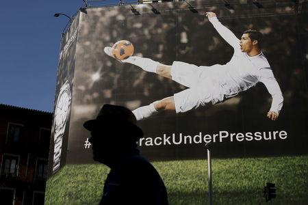 A man walks past a billboard displaying an image of Real Madrid's soccer player Cristiano Ronaldo kicking a ball in Madrid