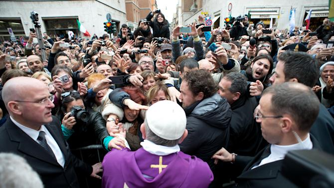 In this photo provided by the Vatican paper L'Osservatore Romano, Pope Francis greets faithful from a side gate of the Vatican, Sunday, March 17, 2013. Pope Francis began his first Sunday as pontiff by making an impromptu appearance to the public from a side gate of the Vatican, startling passersby and prompting cheers, then kept up his simple, spontaneous style by delivering a brief, off-the-cuff homily at the Vatican's tiny parish church. Dressed only in white cassock, Francis waved to the crowd in the street outside St. Anna's Gate and before entering the church, which serves Vatican City State's hundreds of residents, he shook hands of the parishioners and kissed babies. (AP Photo/L'Osservatore Romano)