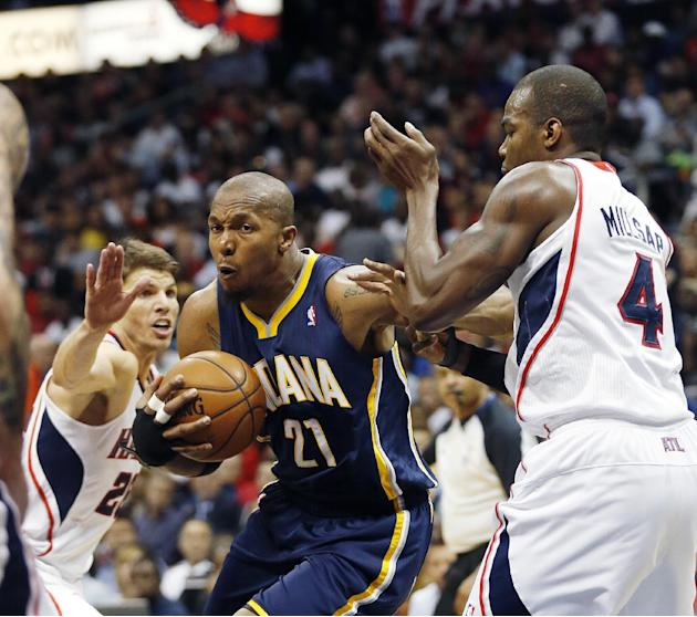 Indiana Pacers forward David West (21) drives between Atlanta Hawks guard Kyle Korver, left, and forward Paul Millsap (4) in the first half of Game 3 of an NBA basketball first-round playoff series on