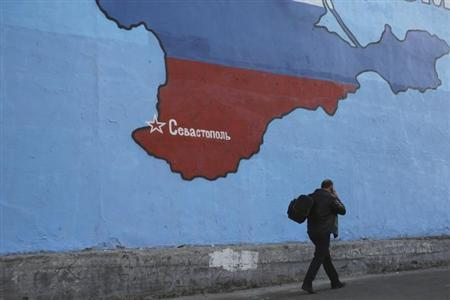 A man passes a mural showing a map of Crimea in the Russian national colours on a street in Moscow March 25, 2014. REUTERS/Artur Bainozarov