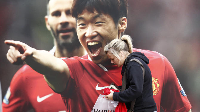 A Manchester United supporter stands in front of a poster of Ji-Sung Park before the team's English Premier League soccer match against Manchester City at Old Trafford Stadium, Manchester, England, Sunday, Oct. 23, 2011. (AP Photo/Jon Super)