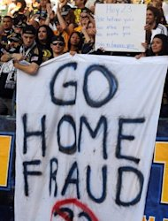 "LA Galaxy fans hold up a sign during a match in 2009 in a protest against David Beckham. Beckham's loans to European teams angered some LA fans who displayed their dislike with signs at games that said ""Go home fraud"" and ""Part time player"""