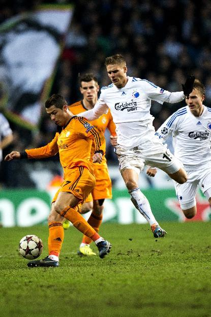 Real Madrid's Christiano Ronaldo, left,  and Gareth Bale background, vie for the ball with FC Copenhagen's Rurik Gislason, centre,  and Pierre Bengtsson during the Champions League, Group B, soccer match between FC Copenhagen and Real Madrid, at Parken in Copenhagen, Denmark, Tuesday Dec. 10, 2013
