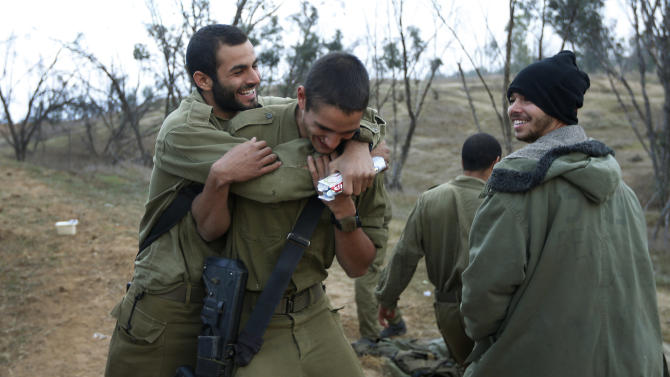 An Israeli soldier, left, hugs a comrade, center, to congratulate him for his birthday at a staging area near the Israel Gaza Strip Border, southern Israel, Thursday, Nov. 22, 2012. A cease-fire agreement between Israel and the Gaza Strip's Hamas rulers took effect Wednesday night, bringing an end to eight days of the fiercest fighting in years and possibly signaling a new era of relations between the bitter enemies. (AP Photo/Lefteris Pitarakis)