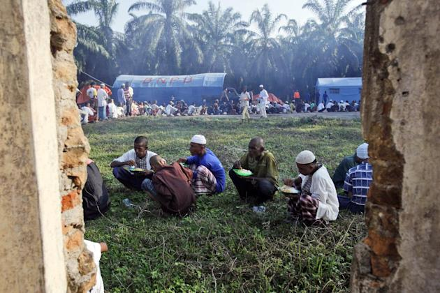 Rohingya migrants have their breakfast at a temporary shelter in Bayeun, Aceh province, Indonesia, Sunday, May 24, 2015. Thousands of migrants - about half of them Bangladeshi and the others minority