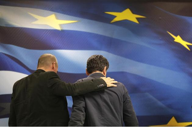 New Greek Finance Minister Euclid Tsakalotos, right, and outgoing Finance Minister Yanis Varoufakis leave together after a hand over ceremony in Athens, in this photo dated Monday, July 6, 2015. The l