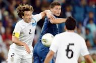 French forward Olivier Giroud (C) clashes with Uruguayan defender Diego Lugano (L) during the friendly football match at the Oceane stadium in Le Havre, western France. The match ended in a 0-0 draw