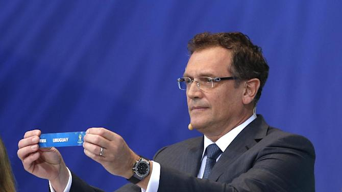 FIFA Secretary General Jerome Valcke shows the ticket of Uruguay during the draw ceremony for the 2014 soccer World Cup in Costa do Sauipe near Salvador, Brazil, Friday, Dec. 6, 2013