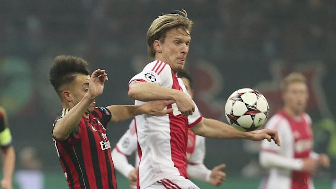 AC Milan forward Stephan El Shaarawy, left, challenges for the ball with Ajax midfielder Christian Poulsen, of Denmark, during a Champions League, Group H, soccer match between AC Milan and Ajax at the San Siro stadium in Milan, Italy, Wednesday, Dec. 11, 2013