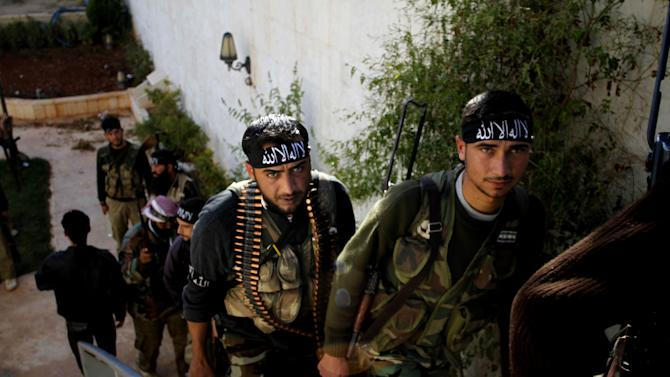 "In this Wednesday, Nov. 14, 2012 photo, Syrian fighters of ""The Beloved of Allah,"" brigade hold their weapons before fighting with government forces on the outskirts of Aleppo. The Beloved of Allah began with ten men, five rifles, one rickety machine gun and a few rocket-propelled grenades soon discovered to be duds. It was born in Maaret Misreen, a town where tractors nearly outnumber cars between the provincial capital of Idlib and the Turkish border to the north. Their leader, 35-year-old Mustafa Filfileh, had no military experience and little idea how to face one of the Mideast's strongest armies. He didn't even know how to drive. They learned fast. In November, the brigade called ""The Beloved of Allah"" braced for its biggest challenge yet, one that would make clear how far its members had come and how far the war had brought them from their former lives. (AP Photo/Khalil Hamra)"